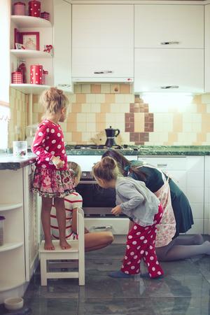 niñas gemelas: Madre con tres niños de cocina pastel de fiesta en la cocina, estilo de vidas foto casual en el interior de la vida real Foto de archivo
