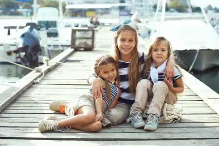 little model: Group of fashion kids wearing navy clothes in marine style walking in the sea port Stock Photo