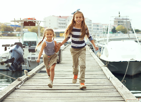 Two fashion kid girls wearing navy clothes in marine style walking in the sea port Stock Photo