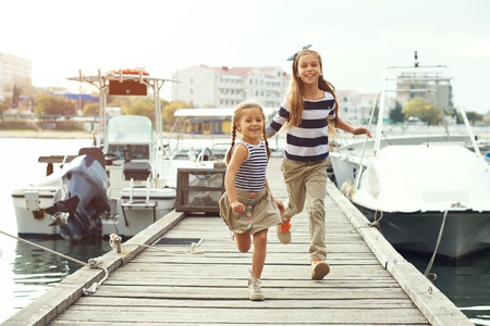 little model: Fashion kids wearing navy clothes in marine style running on wooden berth near the sea
