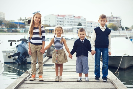 preteens beach: Group of 4 fashion kids wearing navy clothes in marine style posing in the sea port and holding hands Stock Photo