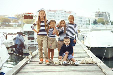 preteens beach: Group of five fashion kids wearing navy clothes in marine style posing in the sea port and holding hands