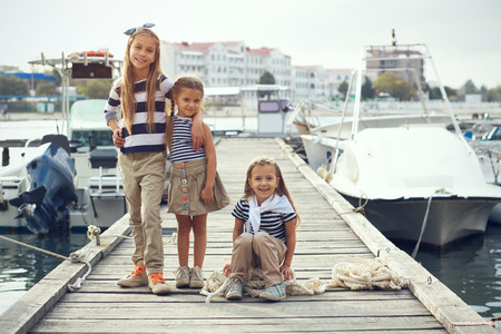 beach model: Group of 3 fashion girls wearing navy clothes in marine style walking in the sea port