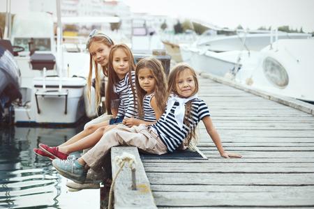 Groep van 4 fashion kinderen dragen marine kleren in maritieme stijl wandelen in de zeehaven Stockfoto