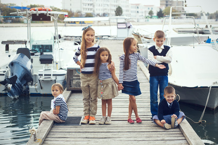 little model: Group of 6 fashion kids wearing navy clothes in marine style walking in the sea port