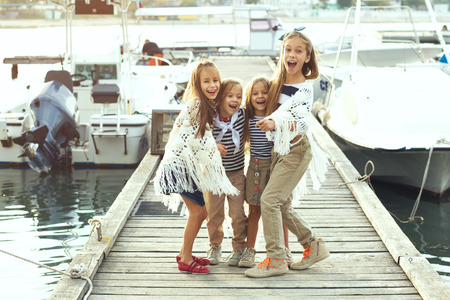 preteens beach: Group of fashion kids wearing navy clothes in marine style having fun in the sea port Stock Photo