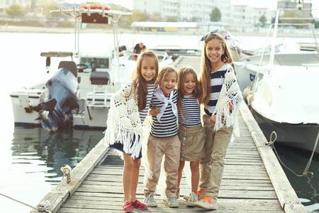 Group of fashion kids wearing navy clothes in marine style walking in the sea port photo