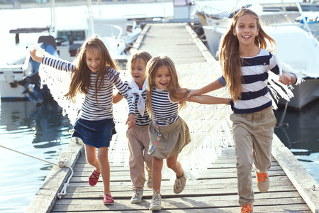 Group of 4 fashion kids wearing striped navy clothes in marine style running in the sea port