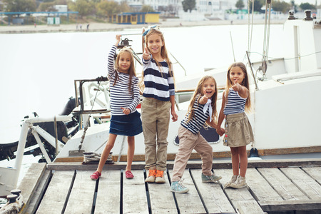 preteens beach: Group of fashion kids sailors wearing navy clothes in marine style enjoying in the sea port