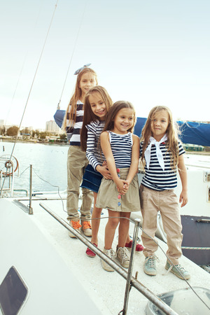 little model: Group of fashion kids wearing navy clothes in marine style posing on white yacht in sea port