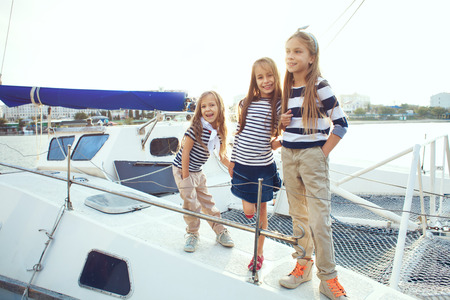 Group of fashion kids wearing navy clothes in marine style posing on white yacht in sea port photo