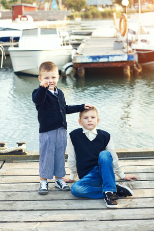 Fashion kid boys wearing navy clothes in marine style posing in the sea port photo
