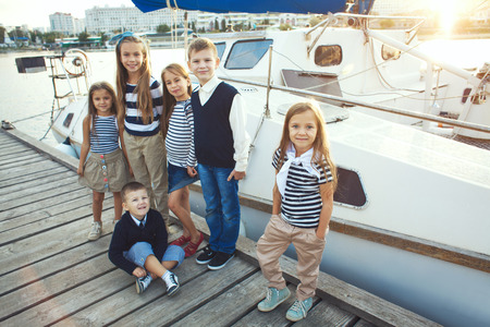preteens beach: Many fashion kids models wearing navy clothes in marine style walking in the sea port near white fashionable yacht Stock Photo