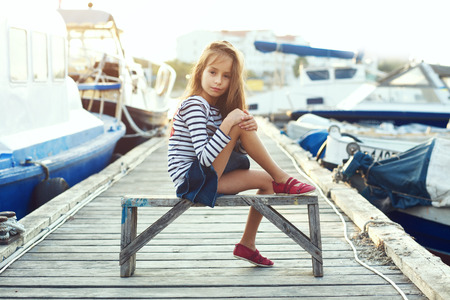 posing: Fashion child wearing navy clothes in marine style posing on wooden berth in sea port