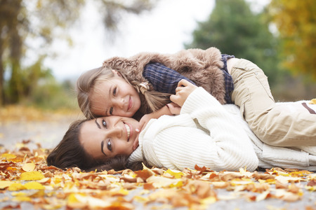 feeling happy: Young mother with her little daughter walking in fall park on yellow fallen leaves one autumn day