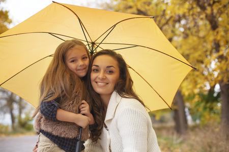 lluvia paraguas: Joven madre con su pequeña hija que recorren en parque de la caída de las hojas amarillas caídas de un día de otoño