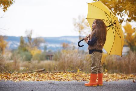 botas de lluvia: Pequeño niño caminando con paraguas bajo la lluvia en el parque de la caída