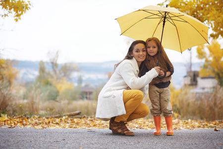 botas de lluvia: Joven madre con su pequeña hija que recorren en parque de la caída de las hojas caídas de color amarillo un día de otoño