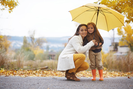 walking boots: Young mother with her little daughter walking in fall park on yellow fallen leaves one autumn day