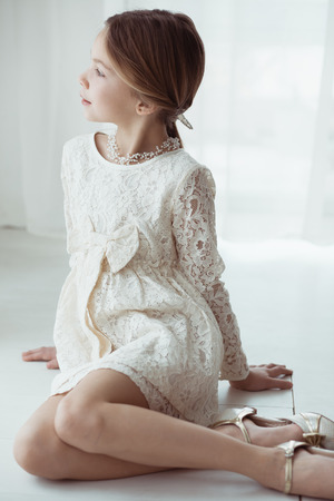Fashion 7 years old model dressed in ivory lace dress pastel tone Stock Photo