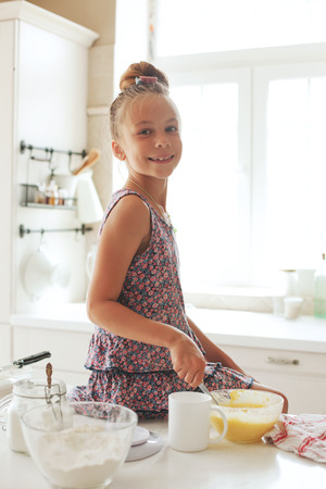 little dough: 7 years old school girl cooking at the kitchen, casual lifestyle photo series