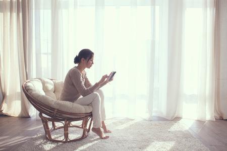 若い女性自宅でタブレット pc を使用して生きていける部屋でリラックスしたウィンドウの前に現代の椅子に座ってください。