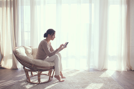 Young woman at home sitting on modern chair in front of window relaxing in her lliving room using tablet pc