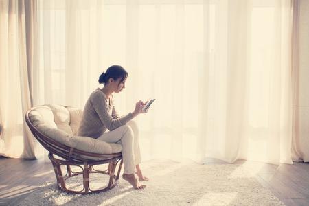 ウィンドウは、タブレット pc を使用して彼女の生きていける部屋でリラックスの前にモダンな椅子に座っている若い女性自宅
