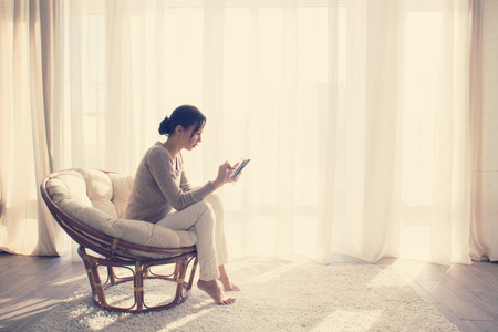 front room: Young woman at home sitting on modern chair in front of window relaxing in her lliving room using tablet pc