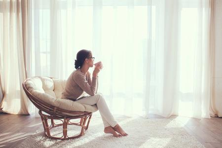 relaxando: Jovem mulher em casa sentado na cadeira moderna na frente da janela que relaxa em seu quarto lliving e beber caf Imagens