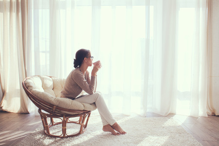 Young woman at home sitting on modern chair in front of window relaxing in her lliving room and drinking coffee or tea
