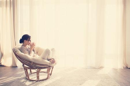 relaxando: A mulher nova em casa sentado na cadeira moderna na frente da janela que relaxa em seu livro de leitura da sala lliving e beber caf