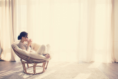 Young woman at home sitting on modern chair in front of window relaxing in her lliving room reading book and drinking coffee or tea Stockfoto