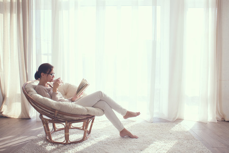 Young woman at home sitting on modern chair in front of window relaxing in her lliving room reading book and drinking coffee or tea Banque d'images