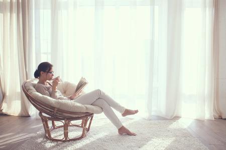 Jonge vrouw thuis zittend op moderne stoel voor het venster te ontspannen in haar lliving kamer leesboek en het drinken van koffie of thee