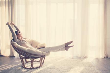 descansando: Mujer joven en casa sentado en silla moderna delante de la ventana se relaja en su libro de lectura de la sala lliving