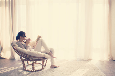 Young woman at home sitting on modern chair in front of window relaxing in her lliving room reading book and drinking coffee or tea Stok Fotoğraf