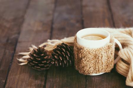 fin de semana: Taza de té caliente con limón vestido con bufanda hecha punto caliente del invierno en la mesa de madera marrón