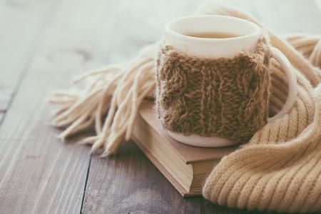Taza de té caliente con limón vestido con bufanda hecha punto caliente del invierno en la mesa de madera marrón, enfoque suave
