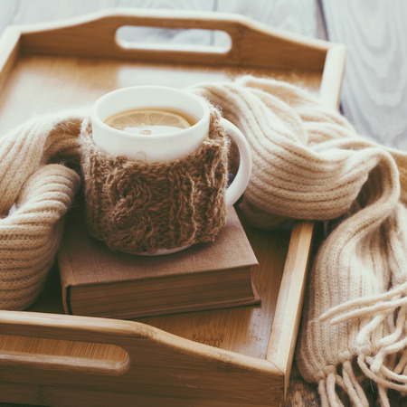 Cup of hot tea with lemon dressed in knitted warm winter scarf on brown wooden tabletop, square photo, soft focus photo
