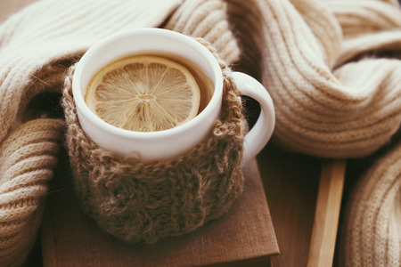hot drink: Cup of hot tea with lemon dressed in knitted warm winter scarf on brown wooden tabletop, soft focus Stock Photo