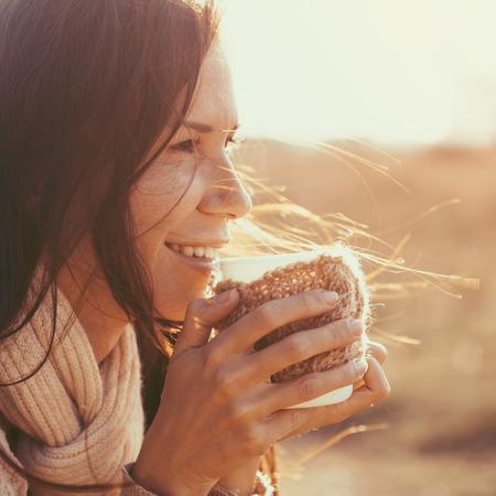 mujer tomando cafe: La mujer llevaba ropa caliente de punto de beber una taza de té o café caliente al aire libre en la luz del sol Foto de archivo