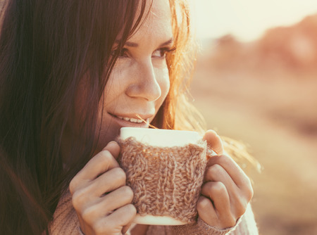 enjoying life: Woman wearing warm knit clothes drinking cup of hot tea or coffee outdoors in sunlight