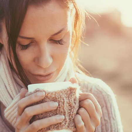 Woman wearing warm knit clothes drinking cup of hot tea or coffee outdoors in sunlight photo