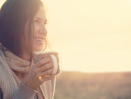 Woman wearing warm knit clothes drinking cup of hot tea or coffee outdoors in sunlight