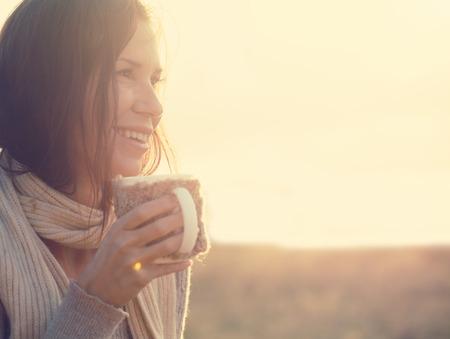 mujer tomando cafe: Mujer que desgasta la ropa caliente de punto de beber una taza de té caliente o un café al aire libre en la luz del sol Foto de archivo