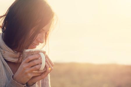 女性の身に着けている暖かいニット服の熱いお茶やコーヒー屋外で日光のカップを飲む 写真素材