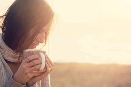 enjoy: Woman wearing warm knit clothes drinking cup of hot tea or coffee outdoors in sunlight