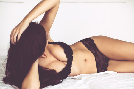 boobs: Boudoir photo of sexy girl wearing stylish black lingerie underwear posing on white bed