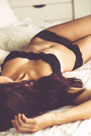 hot breast: Boudoir photo of sexy girl wearing stylish black lingerie underwear posing on white bed